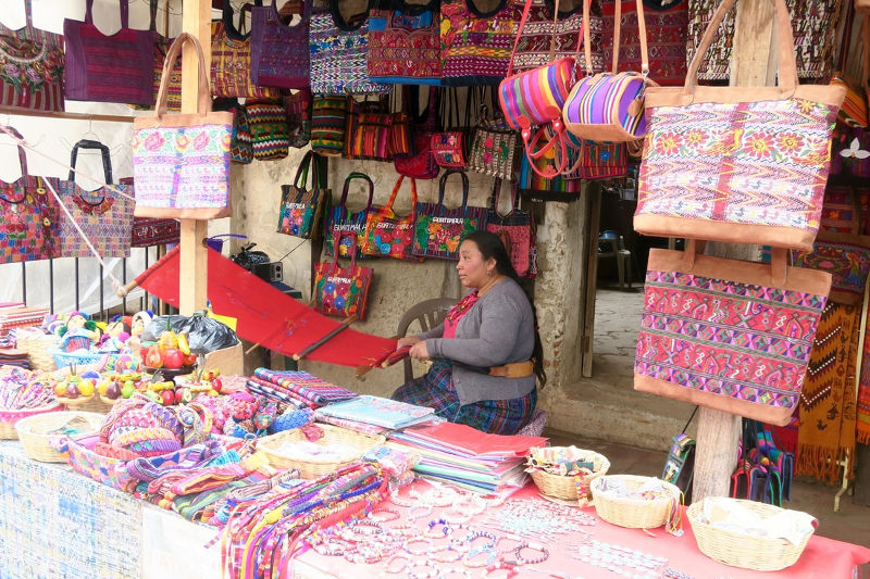 A woman sells colourful handcrafted bags and textiles in a market stall in Guatemala.