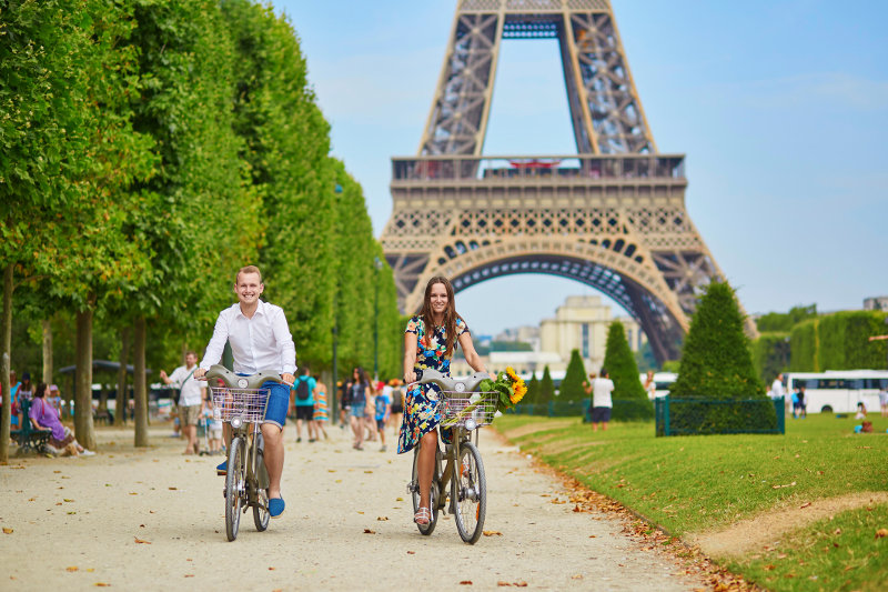 A couple ride bikes past the Eiffel Tower in Paris, France.
