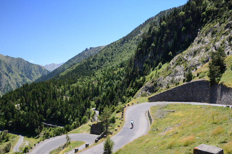 A lone cyclist navigates a winding mountain road in the Pyrenees, France.