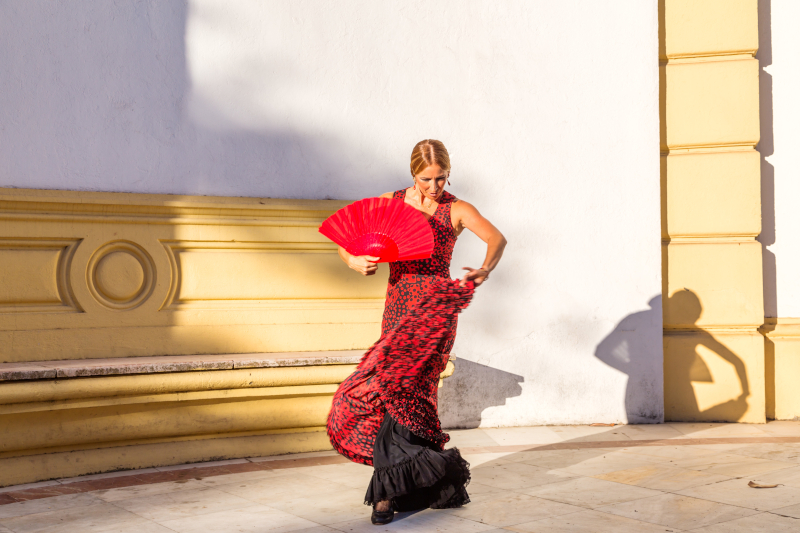 Flamenco dancer in a red dress with a red fan