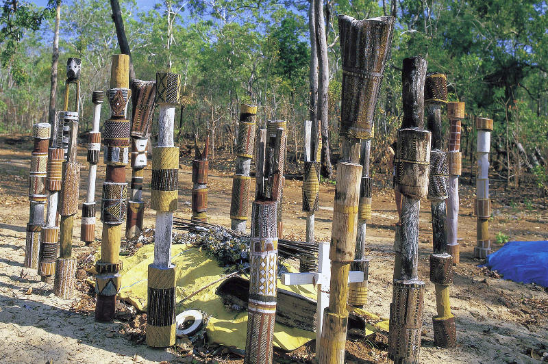 Aboriginal art adorns poles surrounding a burial site on Melville Island in the Tiwi Islands.