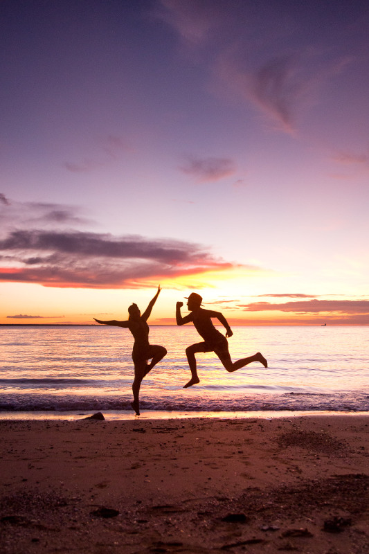 couple jumping on beach infront of sunset in darwin