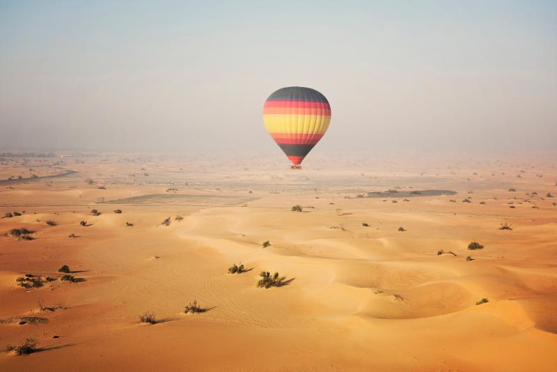 hot air balloon over the dunes and desert near dubai.