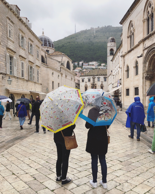 Sheridan and Lucy standing with their back to the camera, holding umbrellas in teh old town of dubrovnik
