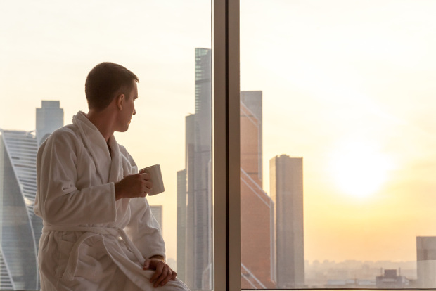 Man in robe with coffee cup observes sunrise early in the morning