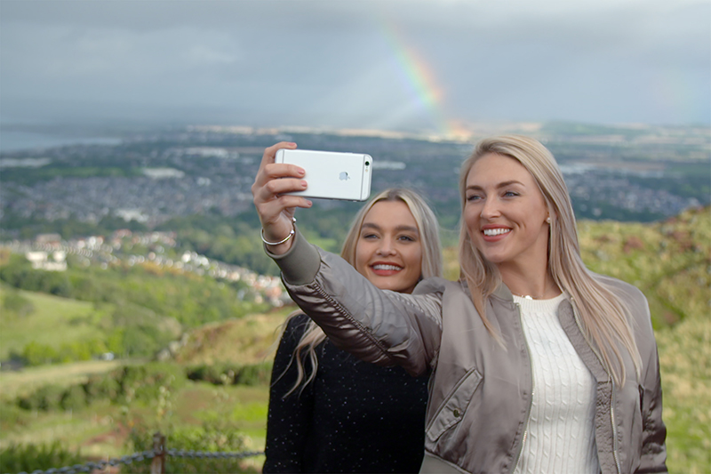 Two women take a selfie at Arthur's Seat, Edinburgh.