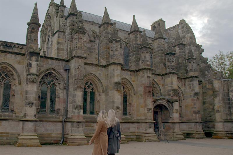 Two women walk around Rosslyn Chapel.