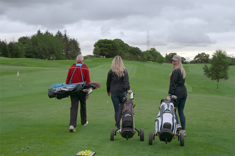 Three people play golf in Scotland.