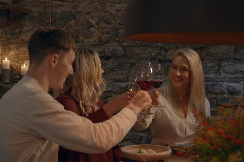 Three people drink wine in an Edinburgh restaurant.
