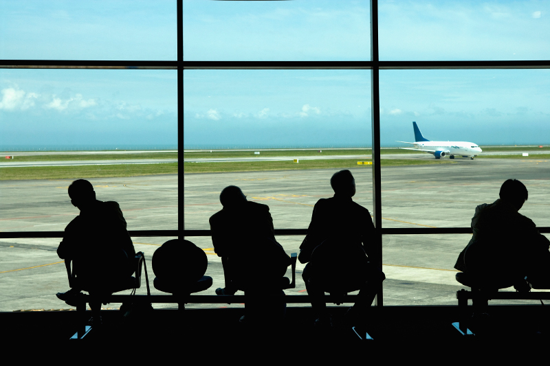 Business travellers waiting at airport.