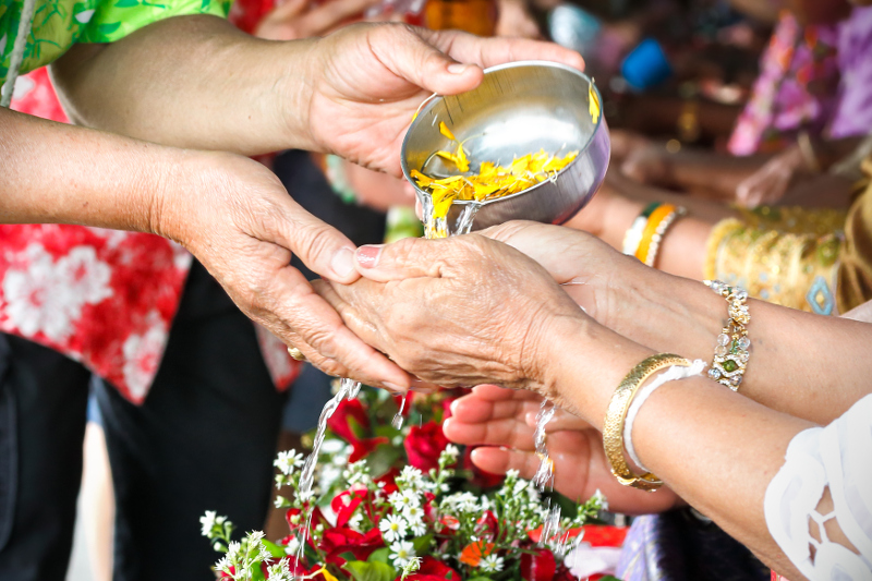 Pouring water infused with flower petals onto hands as part of a Songkran ceremony inside a temple in Thailand.
