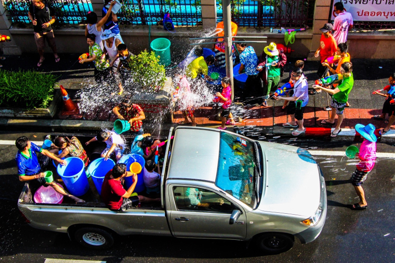 People shooting water pistols at a passing ute filled with people tossing water in bucket, as part of the Songkran festivities in Thailand.