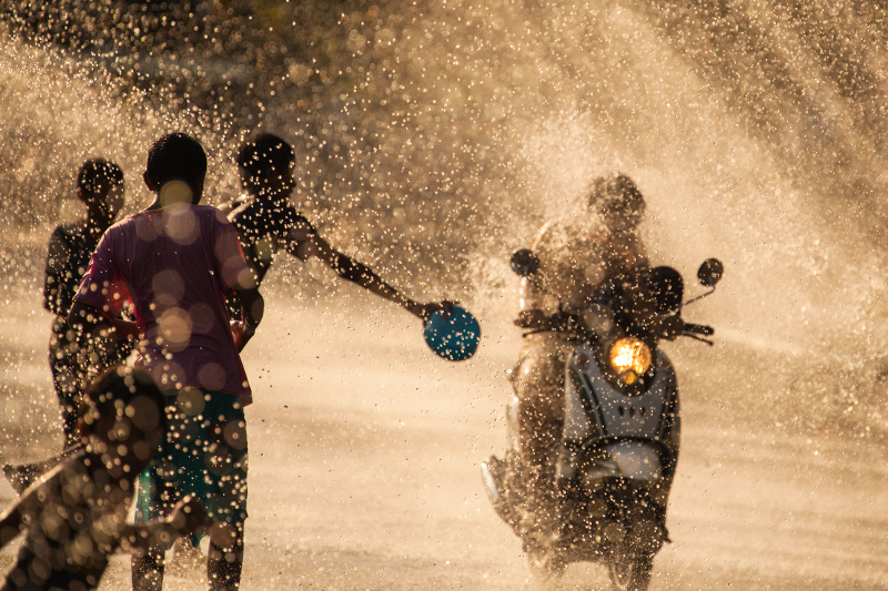 Kids throwing water on a motorcyclist as part of Songkran - the Thai New Year festivities.