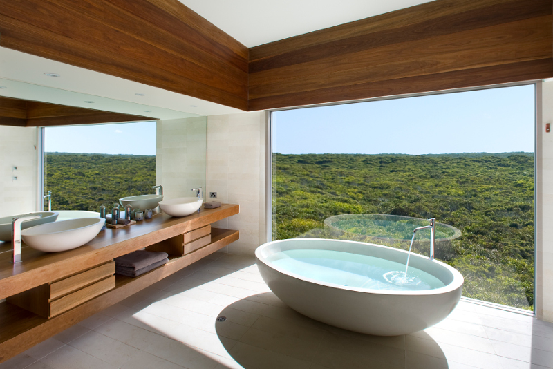 A modern hotel bathtub with beautiful bush vistas out the window, at Kangaroo Island's Southern Ocean Lodge.