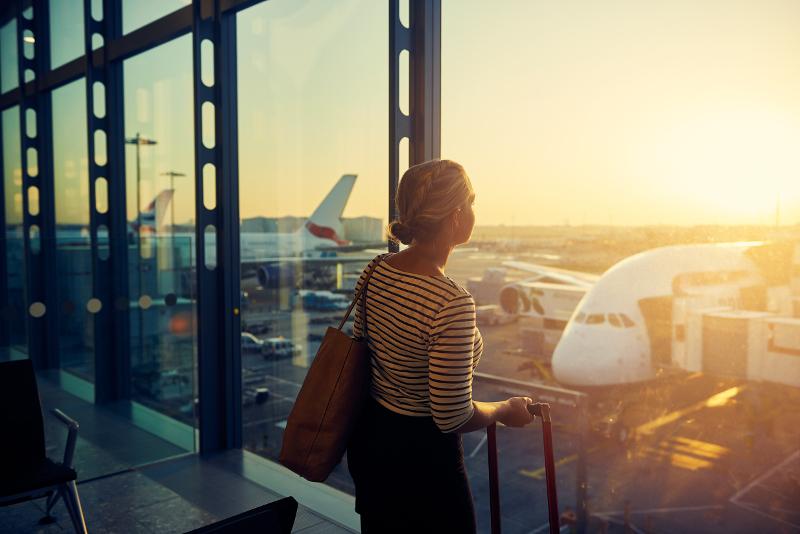 Lady at airport looking at plane.