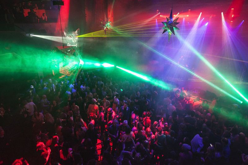 Rave with bright laser lights and people dancing at Dark MOfo festival in Hobart.