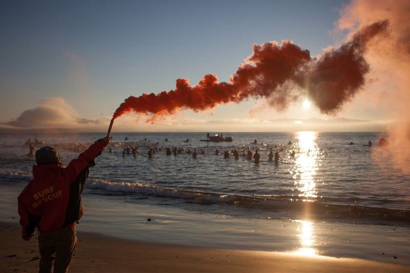 People swimming in the ocean at sunrise in Hobart in the last hours of Dark Mofo festival.