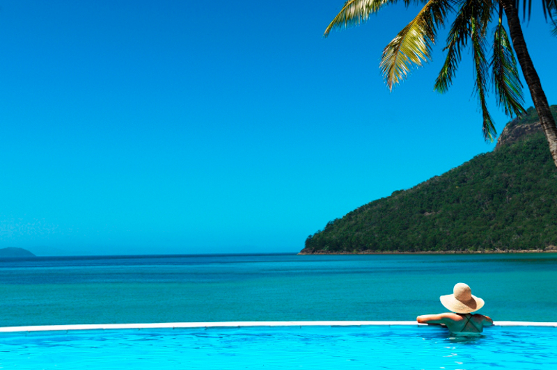 Woman in pool, overlooking the ocean from the pool edge at Hamilton Island.