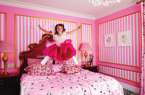 A young girl jumping on a bed in the Eloise suite at The Plaza