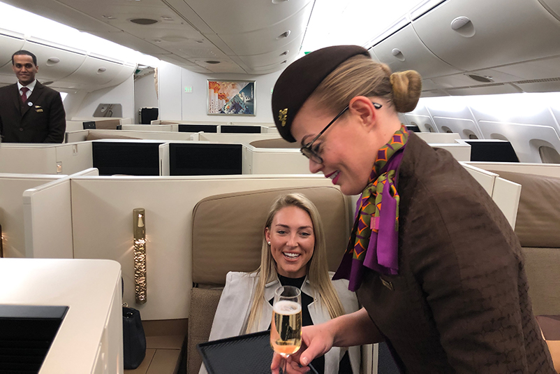 A flight attendant serves a glass of champagne to a female passenger