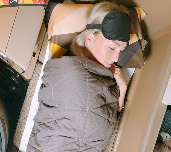 A female sleeps in a fully flat business class bed in business class