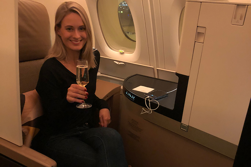 A female with a champagne glass in business class cabin