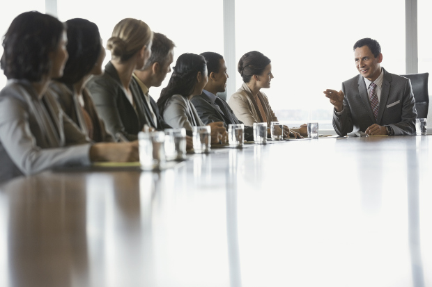 Business man leads meeting in boardroom