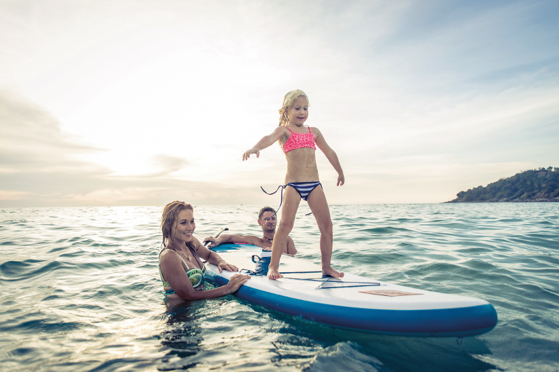 Family teaching a young daughter how to surf