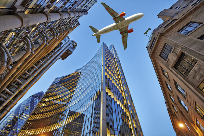 plane flying low over three types of architecture