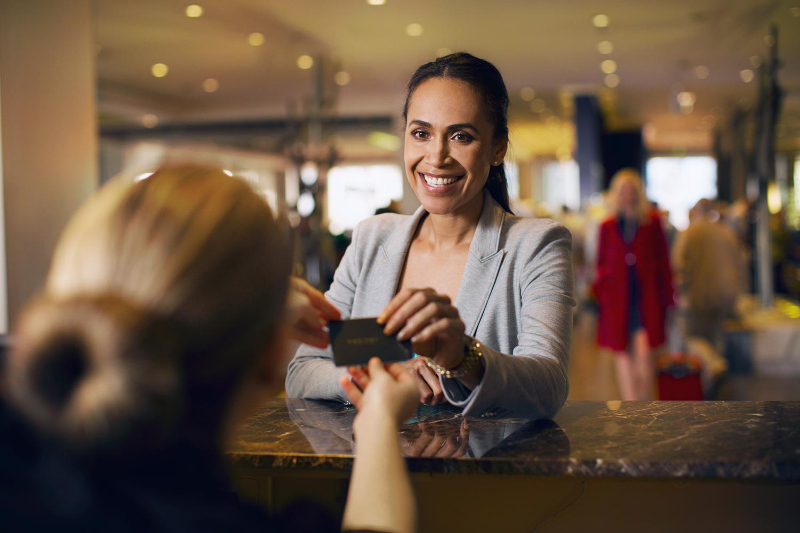 A woman checking into  a hotel