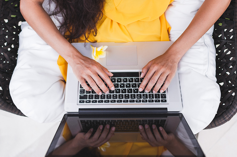 Women working on laptop in a tropical garden setting