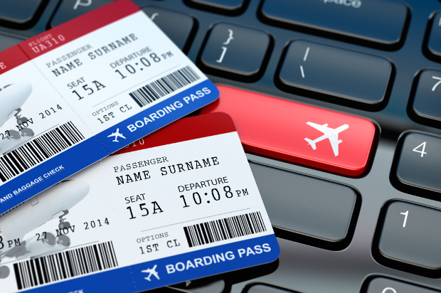 Two first class boarding passes sitting on a computer keyboard
