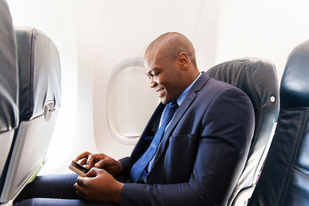 A man sitting in a window seat on an airplane using his phone