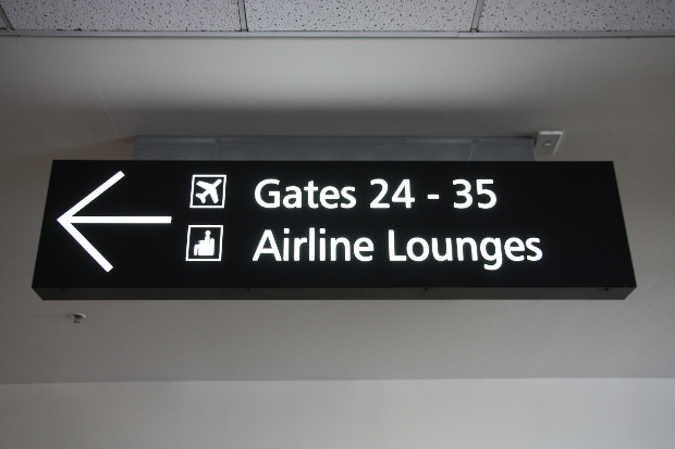 An airport sign pointing to the lounges and gates