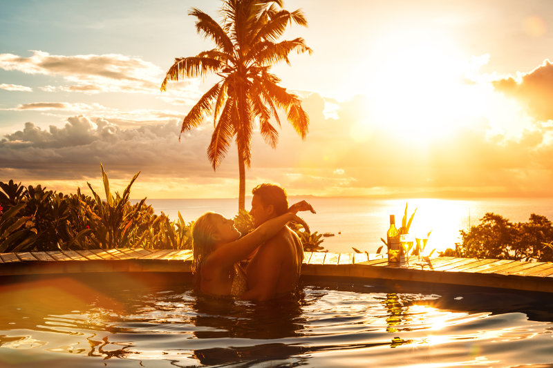 A couple in a pool with an ocean view at sunset in Fiji.