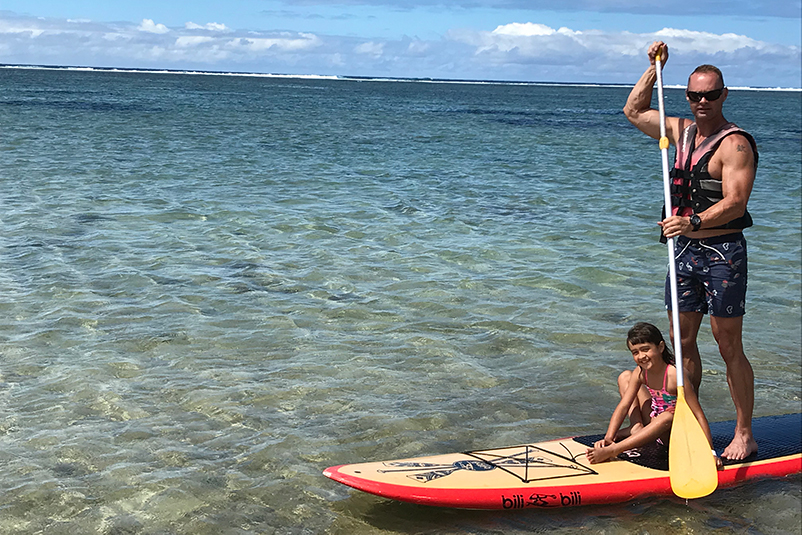 A father and daughter on a SUP board in Fiji