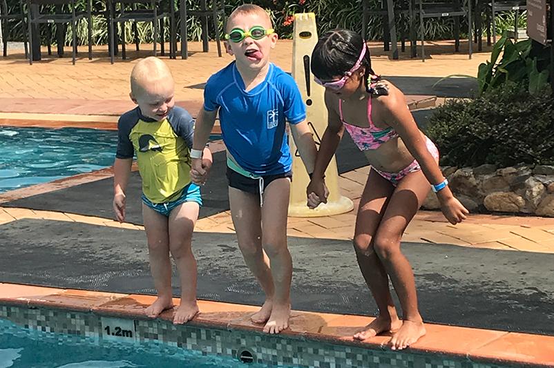 Three kids jump into a pool in Fiji