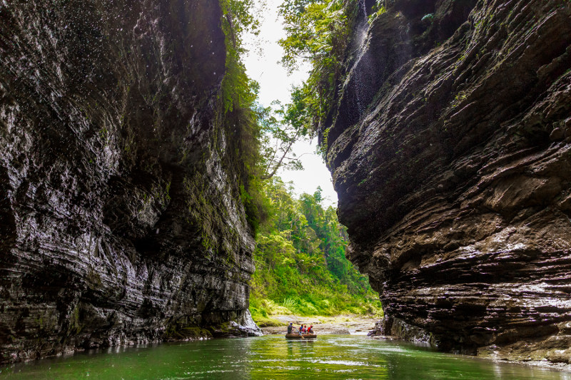 A rafting boat floating between the walls of a canyon