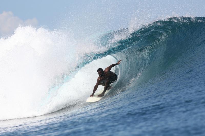 A Fijian surfer rides a wave.