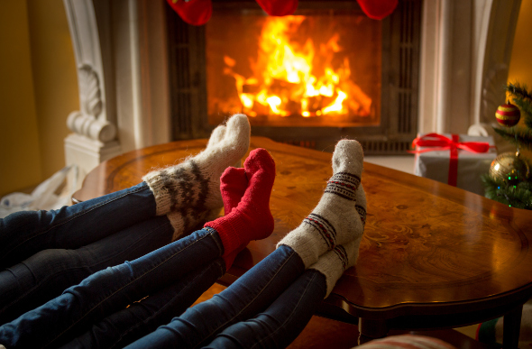A group of friends warming their feet in front of a fireplace
