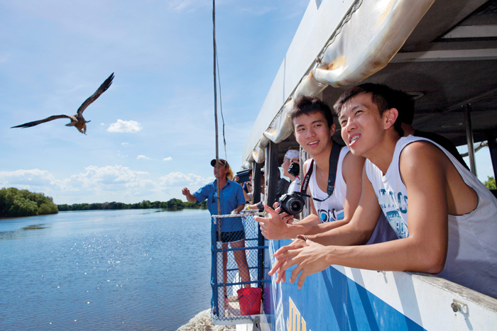 tourists keep an eye out for river creatures