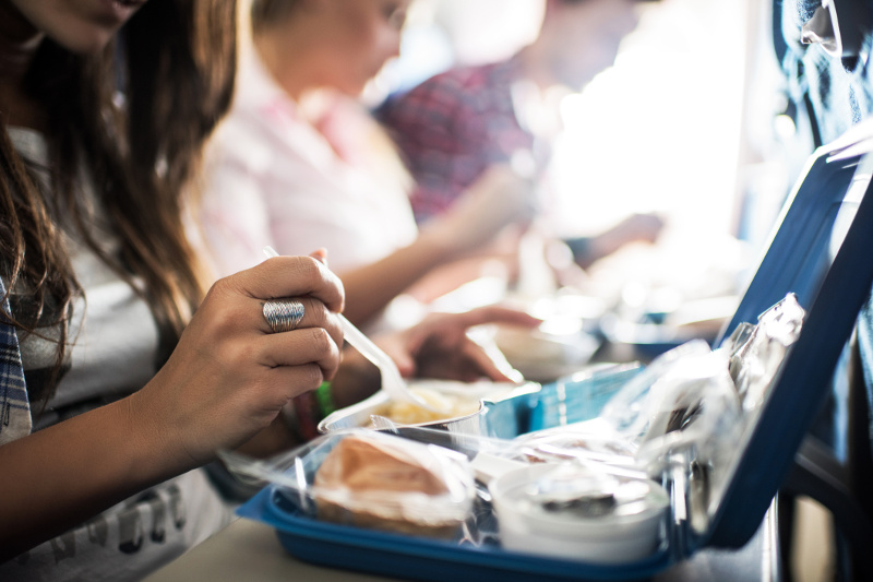 People eating a meal on a plane.