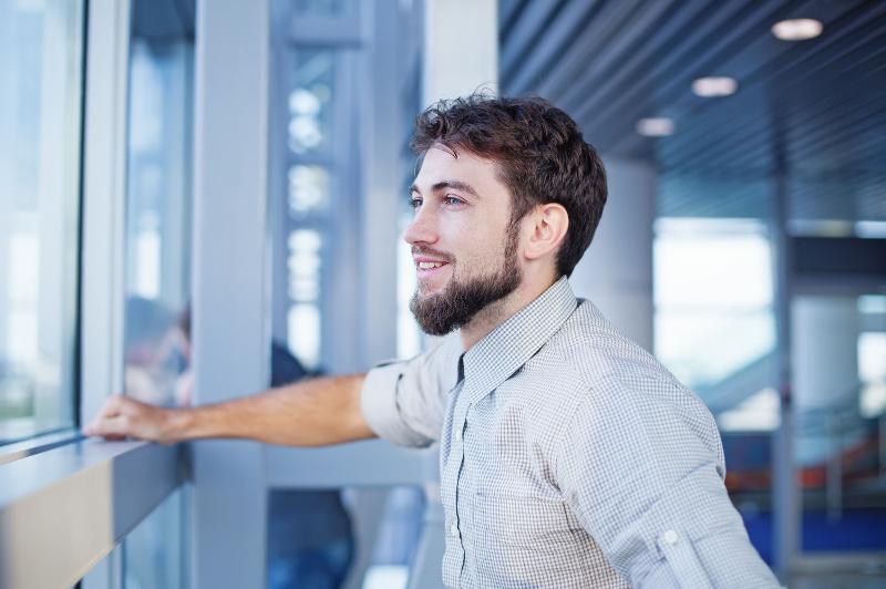 A happy man waits for his flight.