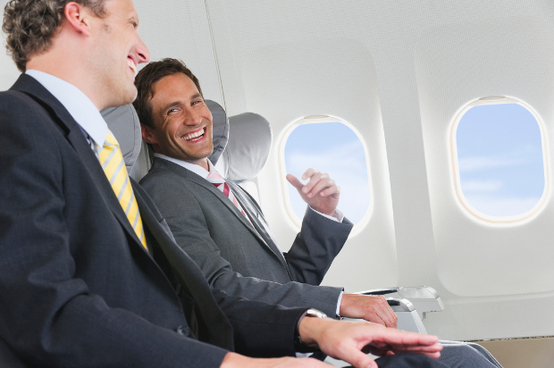 Two men in suits chatting and laughing on a plane