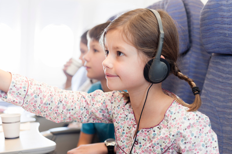 A young girl navigates the inflight entertainment on a plane.