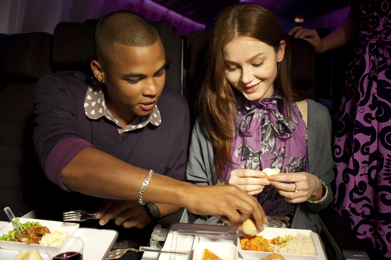 A couple eat a meal on board an Air New Zealand flight.
