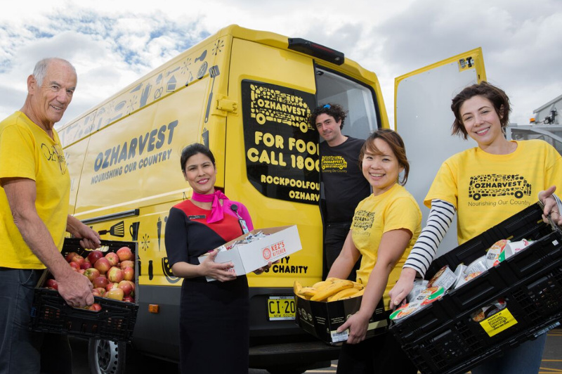 OzHarvest volunteers and a Qantas staffer deliver food from a food rescue van.