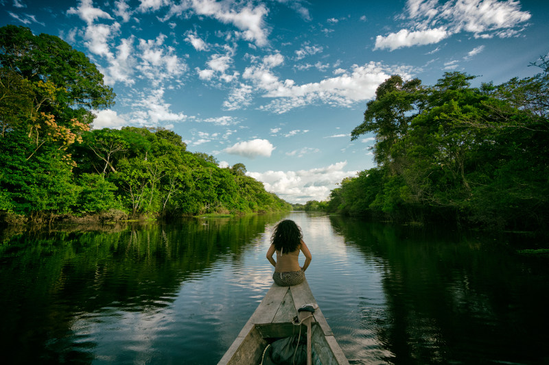 A woman rides in the bow of a traditional boat along the Peruvian Amazon.