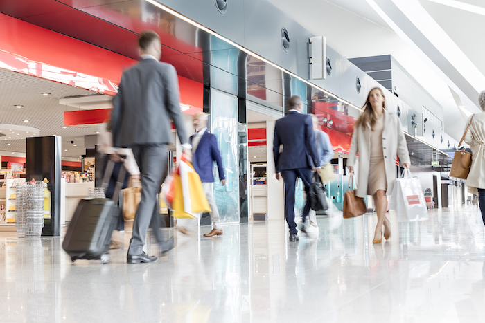 busy travellers in an airport - frequent flyer points - flight centre business travel