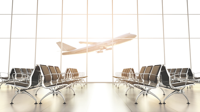 plane taking off seen through airport windows - frequent flyer points - flight centre business travel